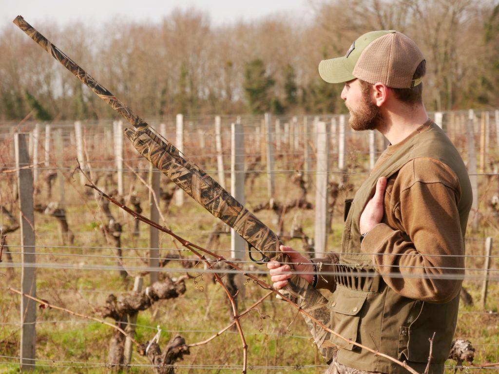 Un chasseur avec un fusil regardant l'horizon dans les vignes. Comment un passionné de chasse peut gagner de l'argent en transmettant sa passion ?