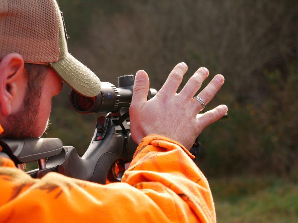 Chasseur en ACCA visant dans une lunette de carabine